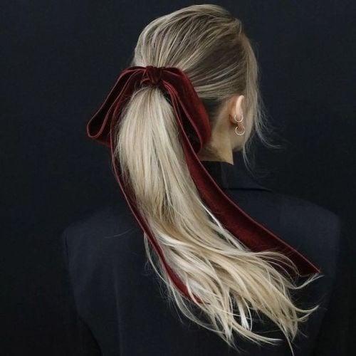 mujer rubia con liston en el cabello cola de caballo