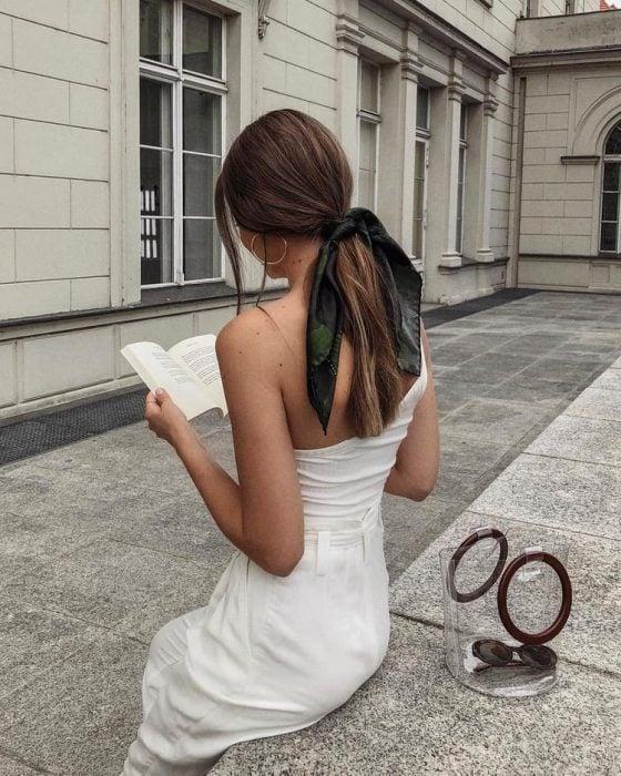 mujer con vestido blanco cola de caballo y pañuelo