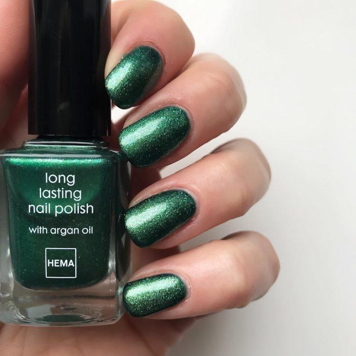 manos de mujer con uñas color verde metálico
