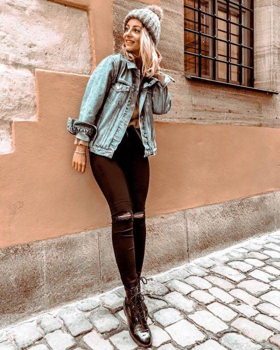 mujer con pantalon negro y chamarra de mezclilla