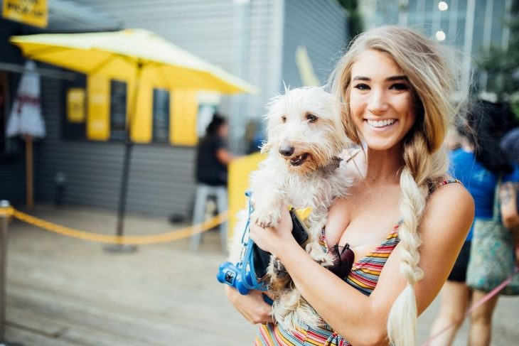 mujer cabello rubio con trenza cargando perro