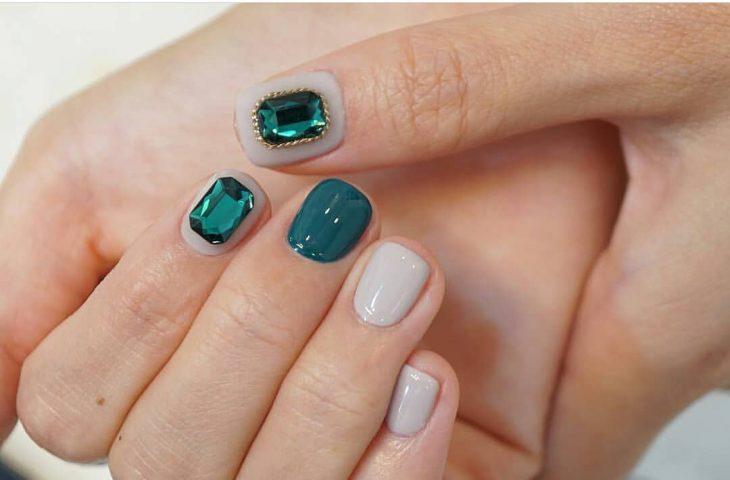 manos de mujer y uñas esmeralda con nude