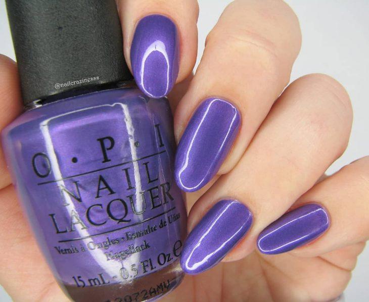 manos de mujer con uñas color morado