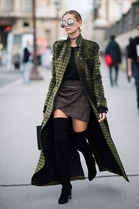 Chica usando falda, abrigo y botas largas