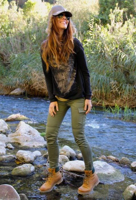 Chica parada en las piedras de un rió mientras usa un atuendo verde y botas timberland