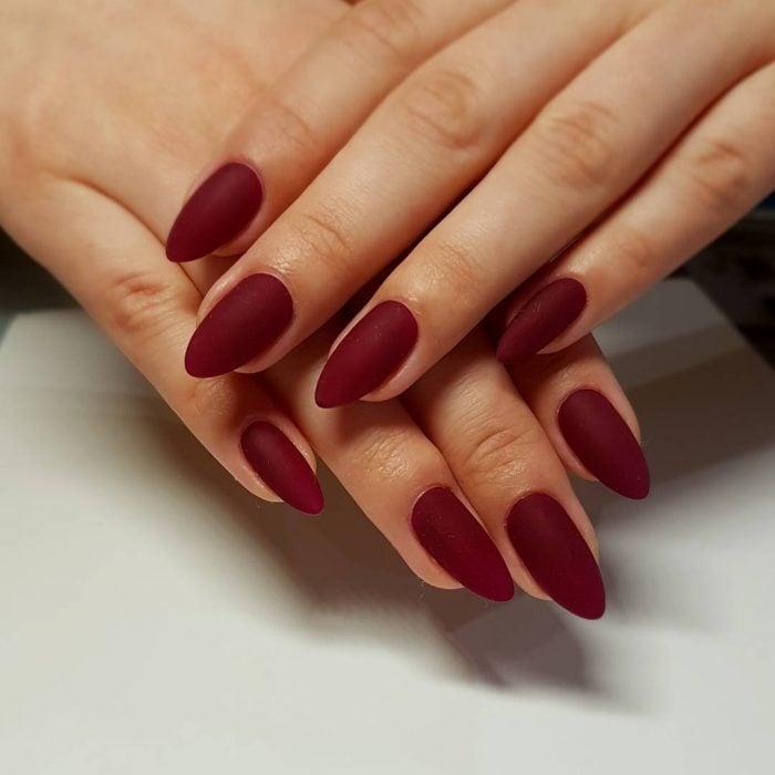 manos de mujer con uñas color vino