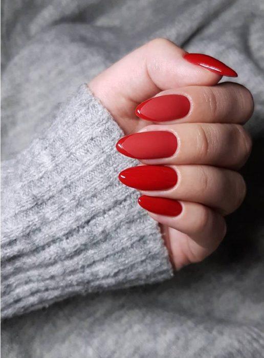 manos de mujer con uñas color rojo