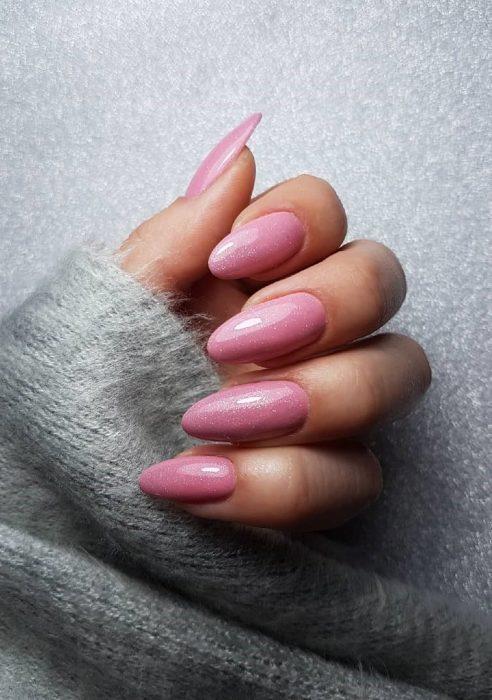 manos de mujer con uñas color rosa