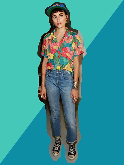 mujer con jeans a la cintura y camisa de flores