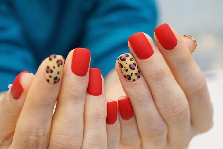 manos de mujer con uñas rojas y leopardo