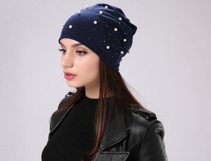 mujer con gorrito azul y perlas