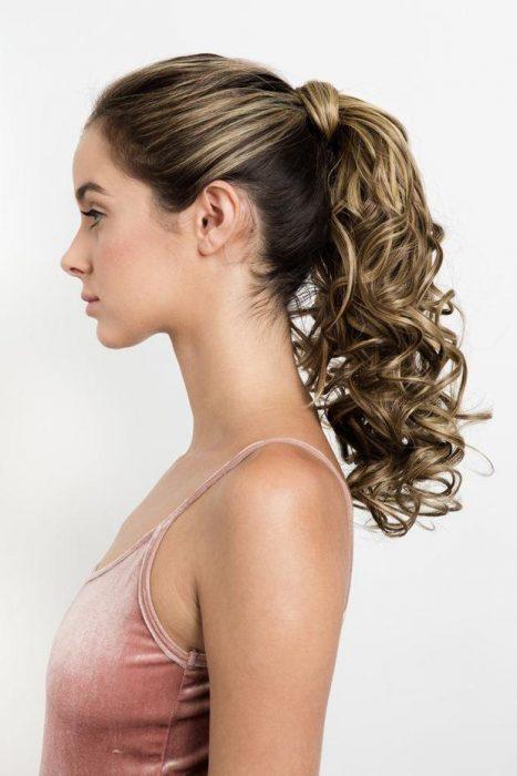 mujer rubia con cabello rizado y cola de caballo