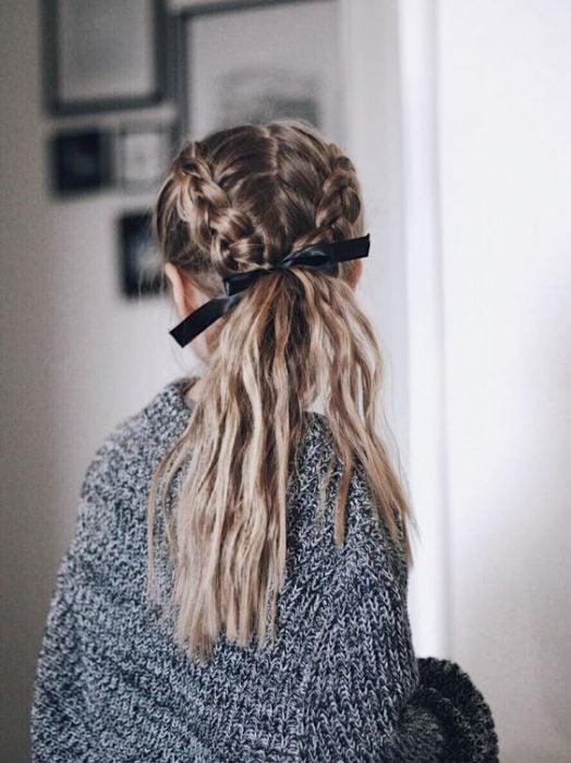 mujer con cabello rubio dos trenzas y coleta de caballo