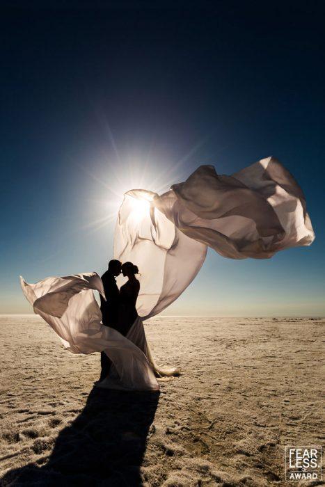 pareja novios con tela en medio de desierto