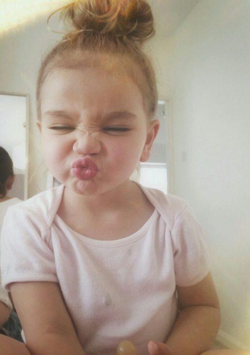 niña con guiño y mandando beso