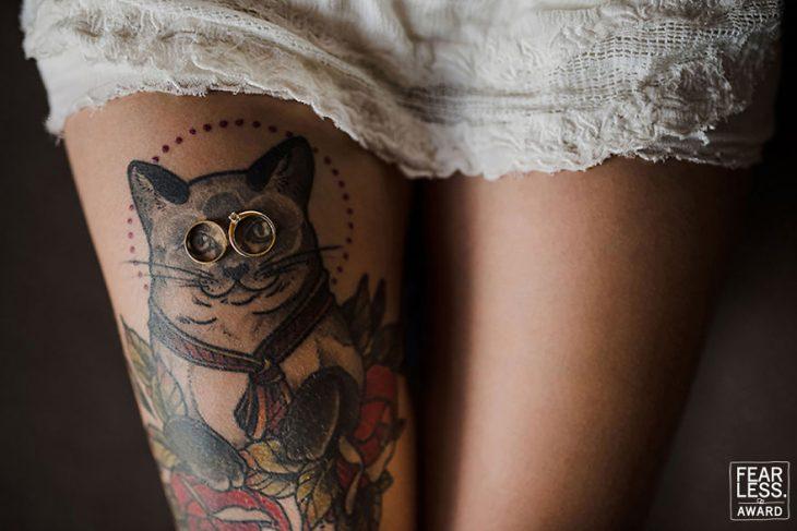 tatuaje de gato en pierna de mujer con vestido blanco y anillos