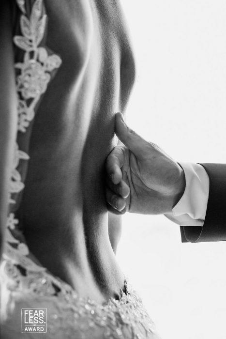 mujer espalda descubierta y mano de hombre