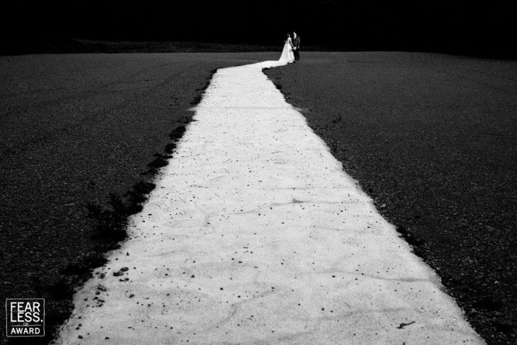 camino blanco entre tierra negra y pareja novios con velo