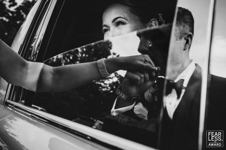 mujer dentro de coche saca brazo y hombre besando mano