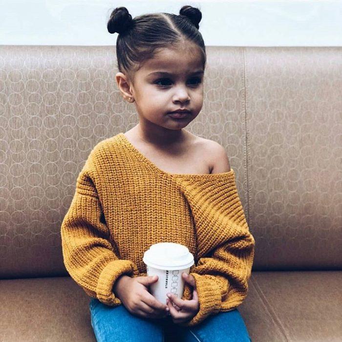 niña con chongos y sueter amarillo