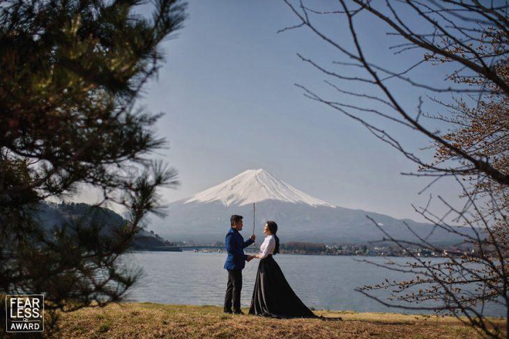 pareja en lago y montaña atrás