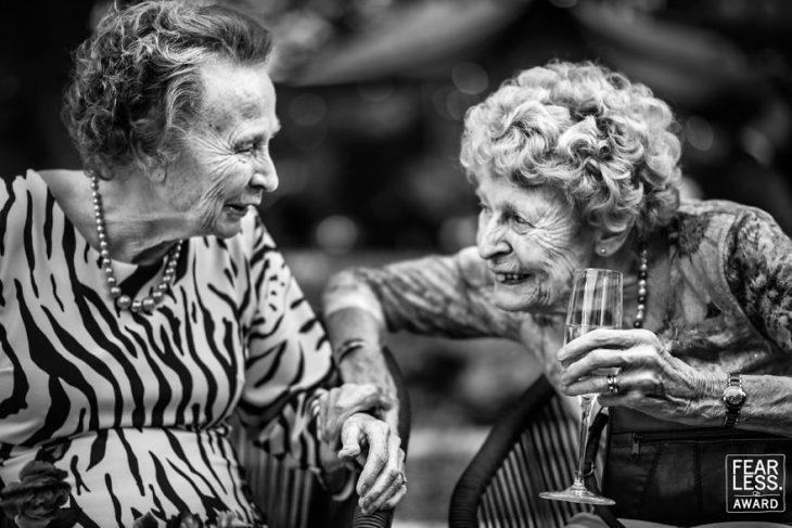pareja de ancianas con copa sonriendo