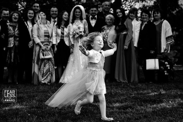 niña con vestido corriendo felliz y pareja novios y familia
