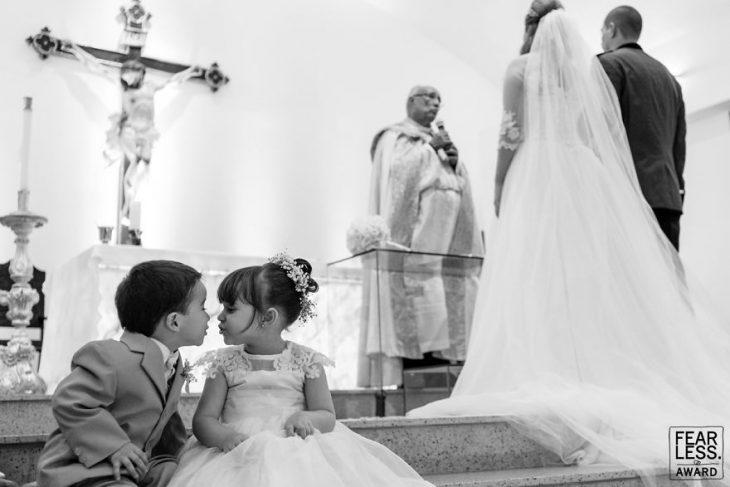 pareja casándose en iglesia y niños sentados beso
