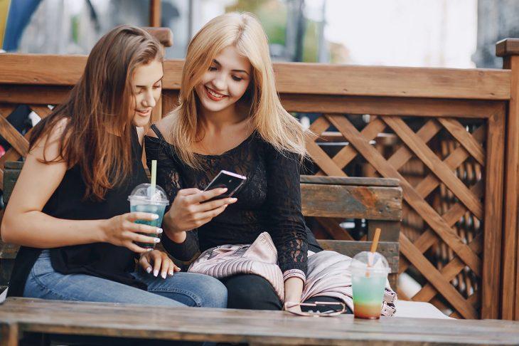 Par de amigas con blusa negra sentadas en una banca tomando una bebida y mirando el celular