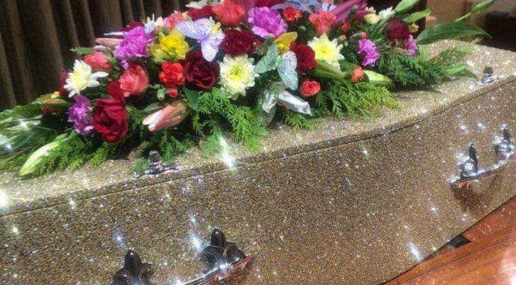 Ataúd brillante con glitter color dorado con arreglo de flores encima