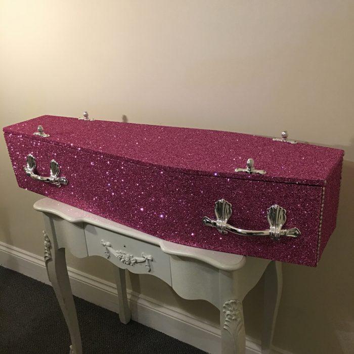 Ataúd brillante con glitter de color rosa y agarraderas plateadas