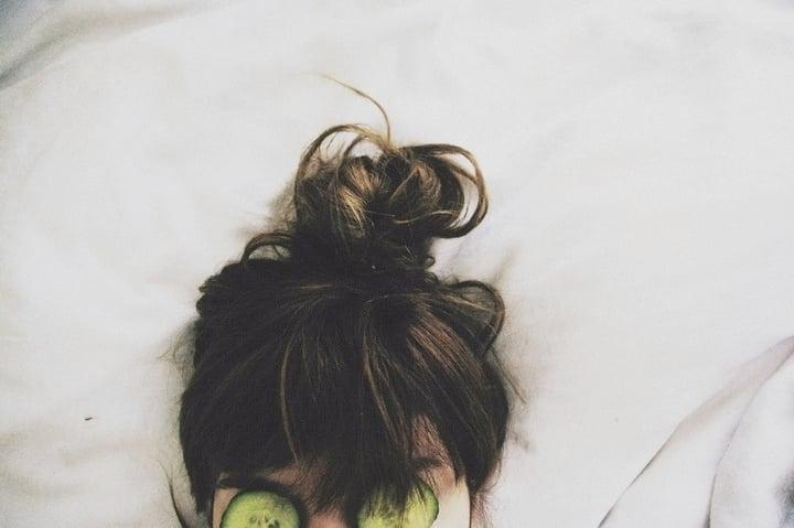 chica con rodajas de pepino en los ojos