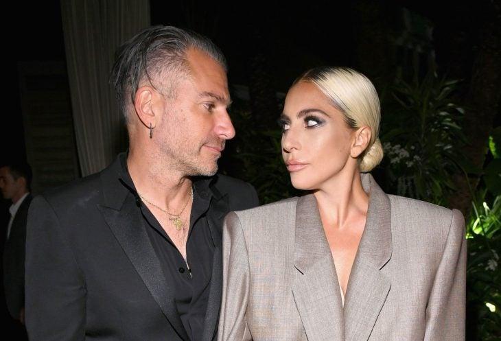 Lady Gaga y Christian Carino, mujer rubia con traje beige y hombre con traje negro