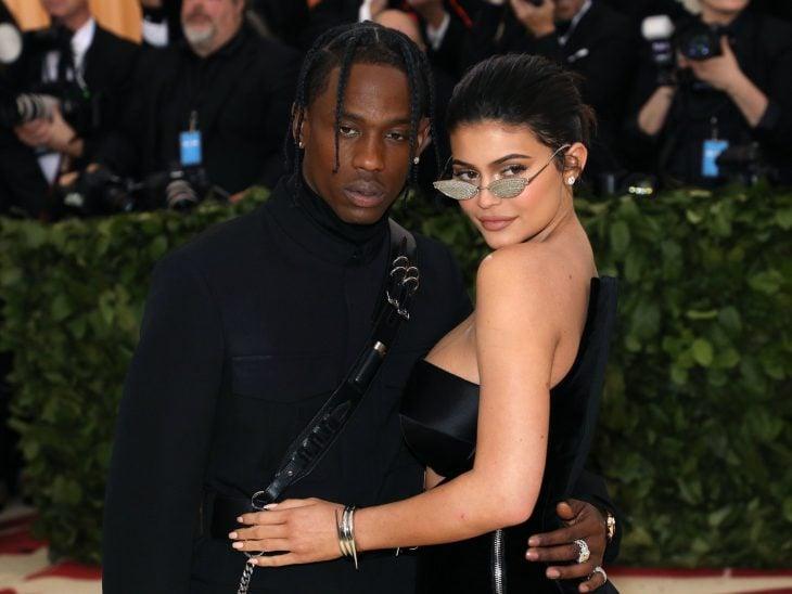 Kylie Jenner y Travis Scott, mujer con vestido negro y lentes de sol y hombre de trenzas con traje negro