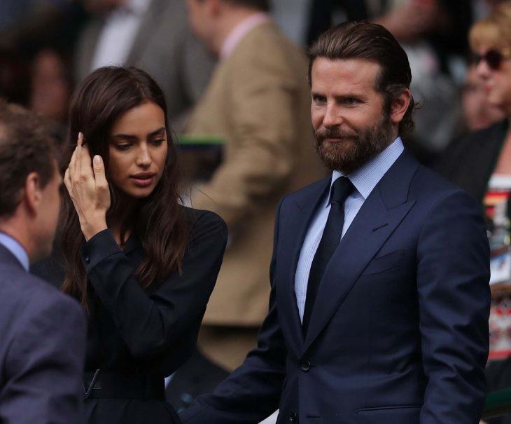Bradley Cooper e Irina Shyk, mujer de cabello largo con traje y hombre con barba y traje