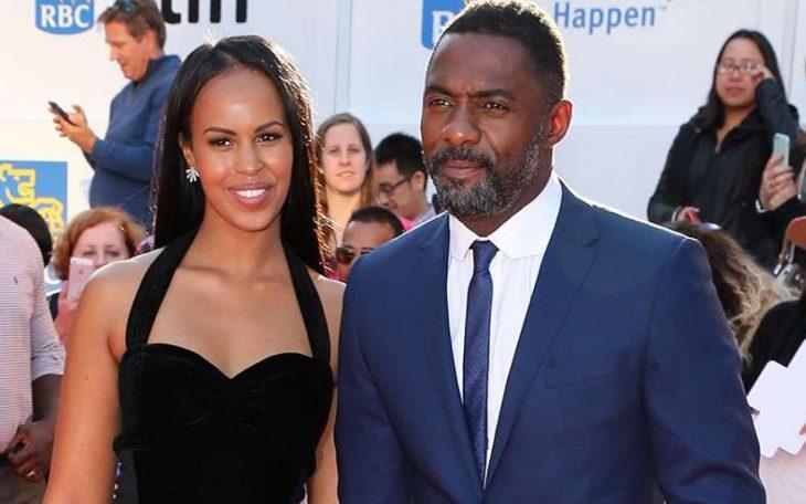Idris Elba y Sabrina Dhowre, mujer afroamericana con vestido negro sonriendo y hombre afroamericano con traje azul y rostro serio