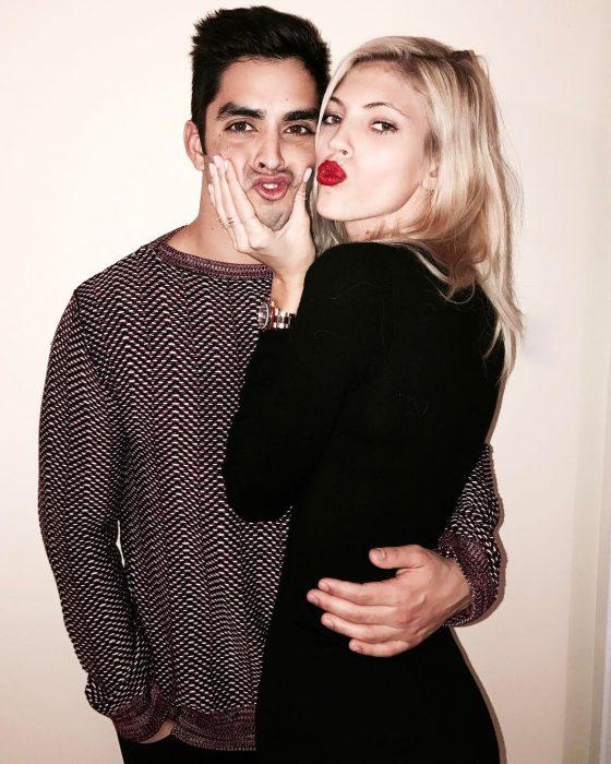 Devon Windsor y Johnny Dez, pareja abrazada, mujer rubia con vestido negro y hombre con suéter haciendo caras graciosas