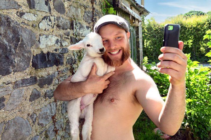 Hombre posando para un calendario irlandés 2019 junto animales de granja