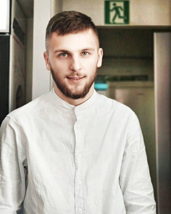 Chico ucraniano de cabello castaño pelirrojo y ojos verdes vestido con una camisa blanca