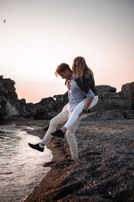 pareja de novios jugando frente un rio