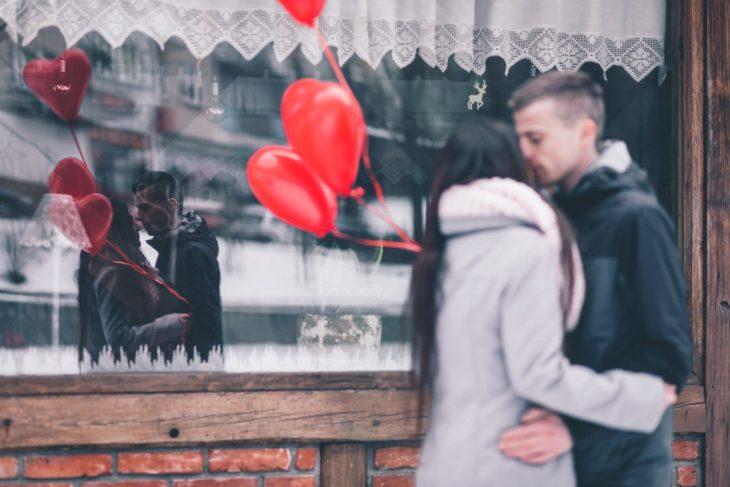 pareja d enovios besándose frente a un cristal