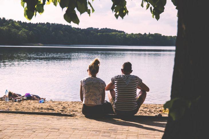 pareja de novios sentados frente a un lago