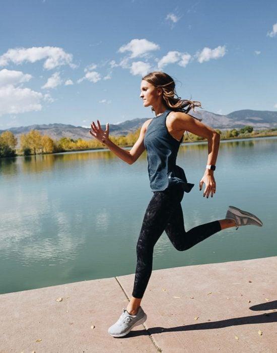Chica de cabello largo en ropa deportiva corriendo al aire libre al lado de un lago