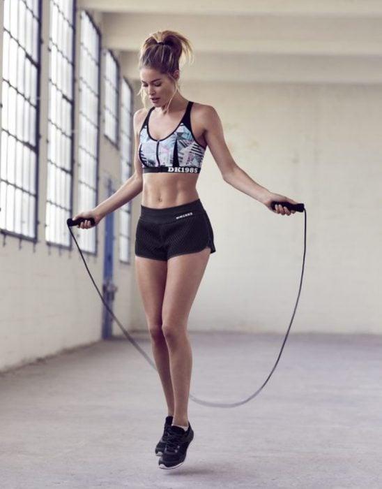 Chica rubia con traje deportivo saltando la cuerda en un cuarto solo
