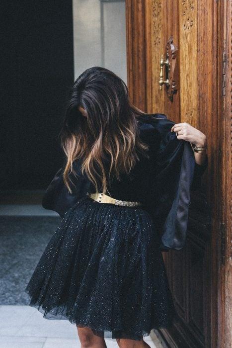 Chica de cabello castaño con luces usando vestido negro con brillos, cinto dorado y chaqueta negra