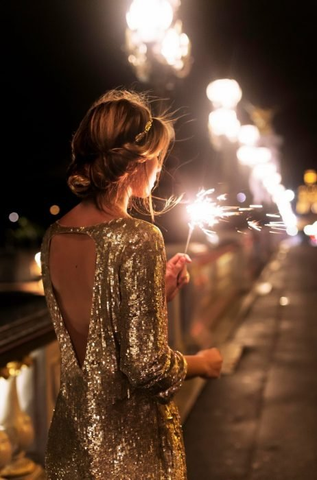 Chica rubia de cabello recogido usando un vestido de lentejuelas dorado con una luz de bengala