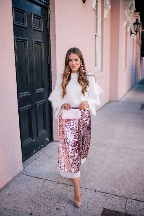 Chica de cabello rubio y largo vistiendo un suéter blanco y una falda de lentejuelas rosa