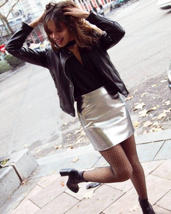 Chica de cabello castaño con una minifalda plateada, blusa negra, chaqueta negra y zapatillas de tacón ancho