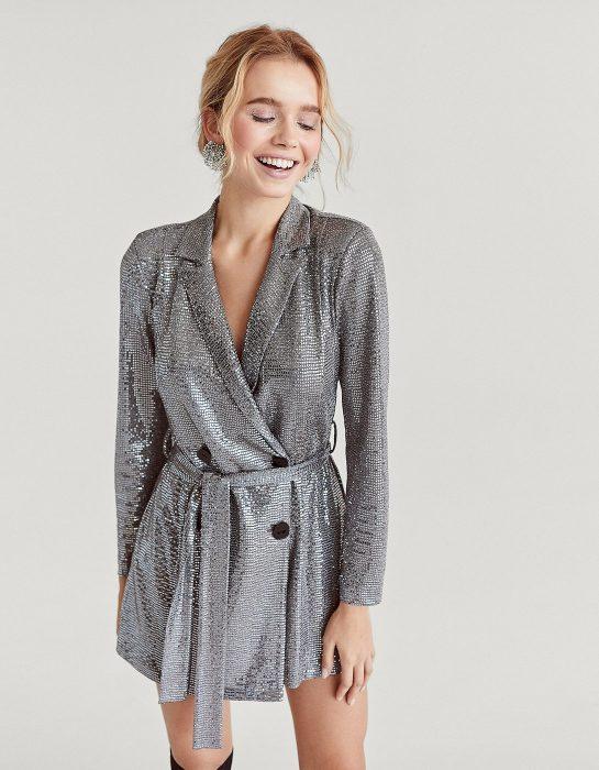 Chica de cabello rubio recogido en un chongo, sonriendo y usando un vestido de brillos plateado