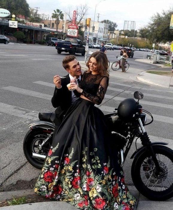Pareja vistiendo ropa elegante sentados sobre una motocicleta en la calle